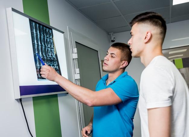 O fisioterapeuta com paciente masculino novo examina a imagem de ressonância magnética.