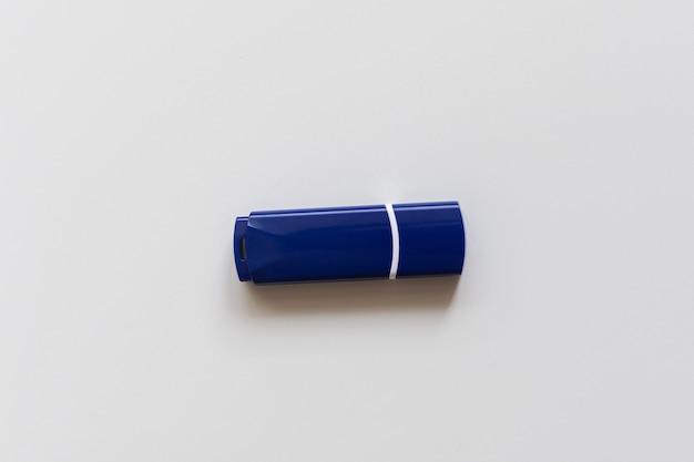 O flash drive azul em uma superfície branca