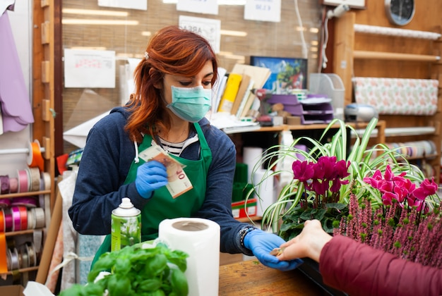 O florista da loja recebe um pagamento de um cliente usando máscara e luvas