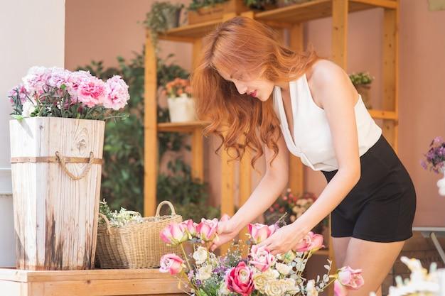O florista de sorriso da mulher arranja flores bonitas na loja de flor