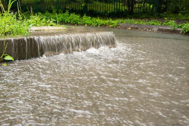O fluxo de água desce para a zona pedonal. tempo chuvoso de outono. chuva pesada. cenas de rua na chuva.