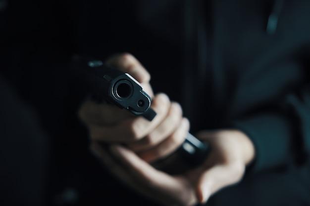 O focinho da arma está apontado para a câmera recarregando o homem do close up da arma insere o tambor de cartuchos no pis ...