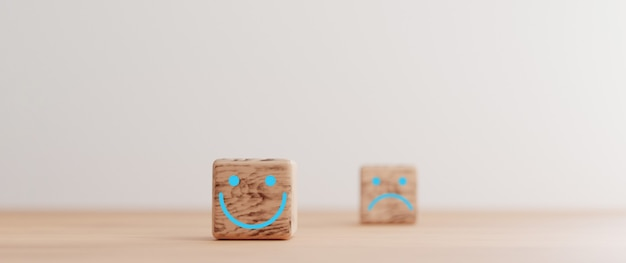 O foco da tela de impressão do rosto de sorriso em um bloco de cubo de madeira e desfocagem do rosto de tristeza no lado escuro para avaliação de atendimento ao cliente e conceito de mentalidade de emoção por renderização 3d.