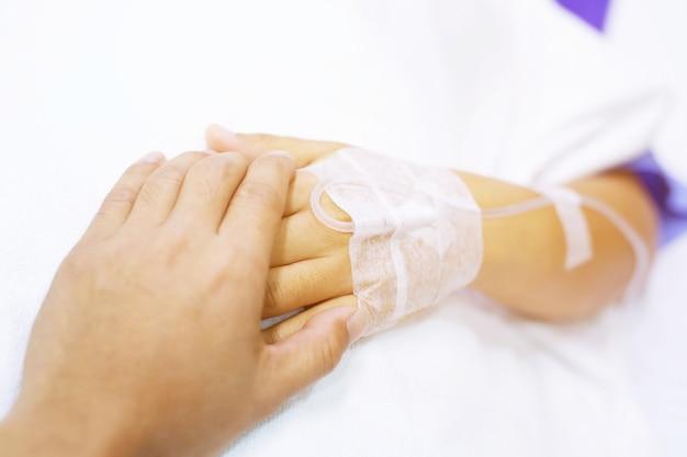 O foco de close-up no aperto de mãos de um paciente doente encoraja o encorajamento na cama na enfermaria do hospital.