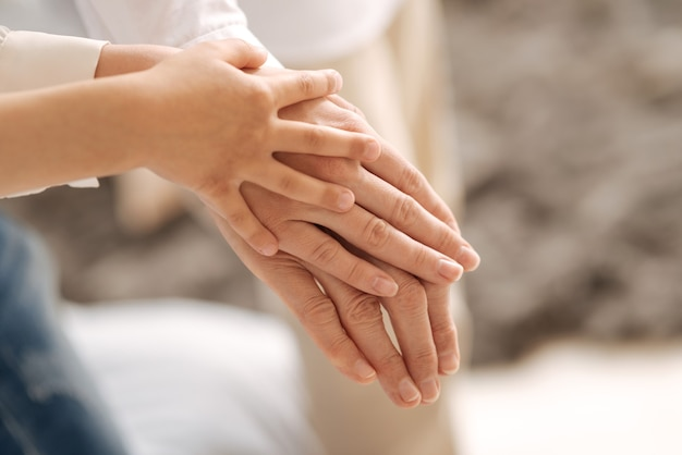 O foco está nas três mãos de mulheres pertencentes a diferentes gerações e sendo colocadas umas sobre as outras, começando da mais velha na parte inferior até a
