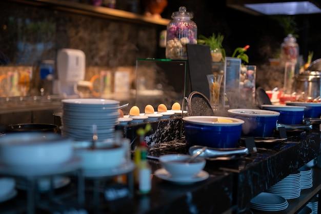 O foco selecionado de ferver ovos na placa na linha do bufete para o café da manhã.