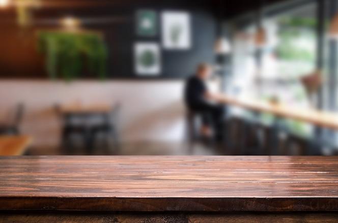 O foco selecionado é uma mesa de madeira marrom vazia e uma cafeteria ou restaurante desfocam o fundo com a imagem do bokeh. para a sua exibição de fotomontagem ou produto.