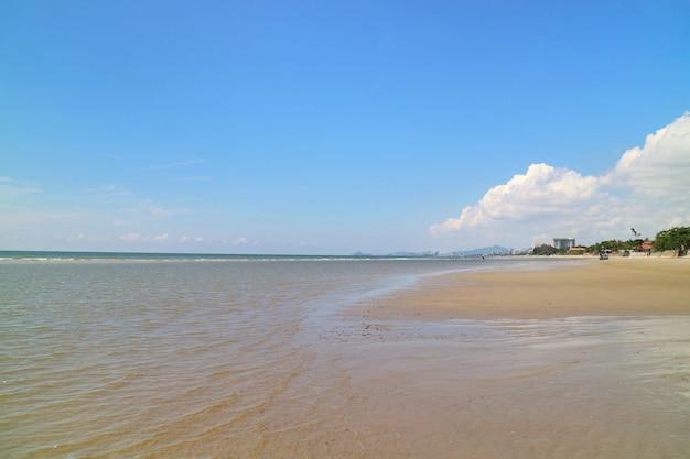 O foco suave das ondas bate na praia com areia e o céu azul com reflexão.