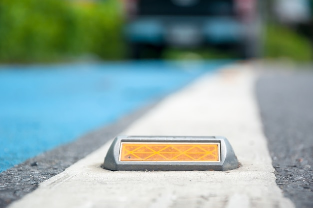 O foco suave de refletor ou parafuso prisioneiro na estrada de asfalto
