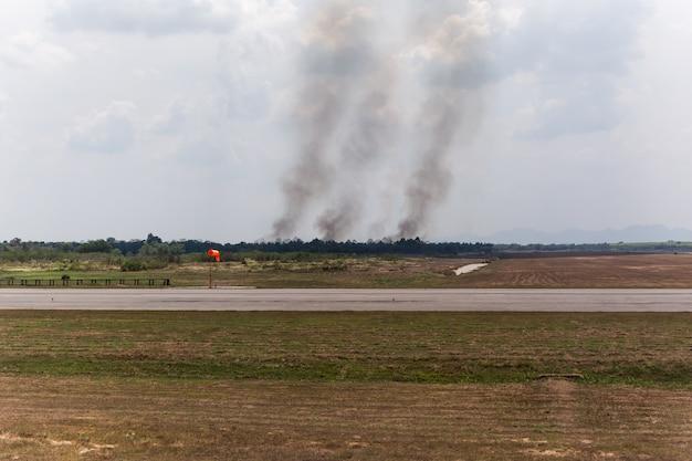 O fogo queima perto do aeroporto com a fumaça do fogo causa poluição ruim.