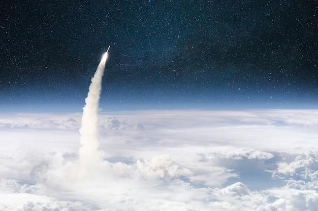 O foguete decola através das nuvens e voa para o espaço sideral. lançamento bem-sucedido da nave espacial. planeta terra em órbita