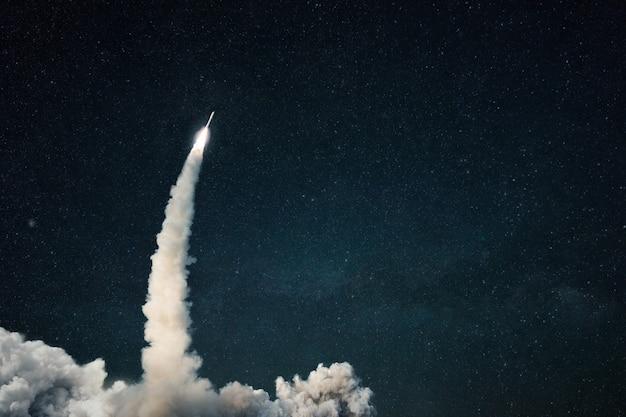 O foguete decola para o espaço. lançamento de nave espacial com fumaça no céu estrelado. espaço e papel de parede de viagens. copie o espaço para design e texto