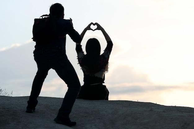 O fotógrafo atira em uma garota com as mãos em forma de coração contra o céu