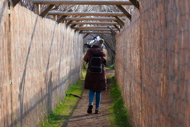 O fotógrafo de pássaros caminhando em um caminho e voltando para casa