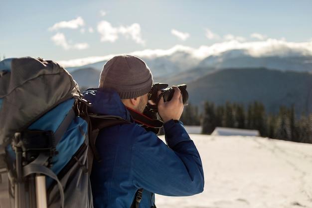 O fotógrafo de turista homem alpinista em roupas quentes com mochila e câmera tirando foto do vale nevado e picos de montanhas arborizadas paisagem sob o céu azul em dia ensolarado de inverno frio.