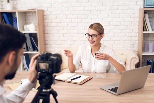 O fotógrafo dispara na mulher de negócios para o podcast do negócio.