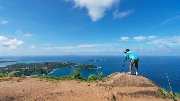 O fotógrafo do viajante tira uma foto ou grava um vídeo da paisagem no ponto de vista phahindum, ponto de referência popular em phuket tailândia ponto de vista para ver a praia promthep do cabo naiharn e a praia yanui vista incrível.