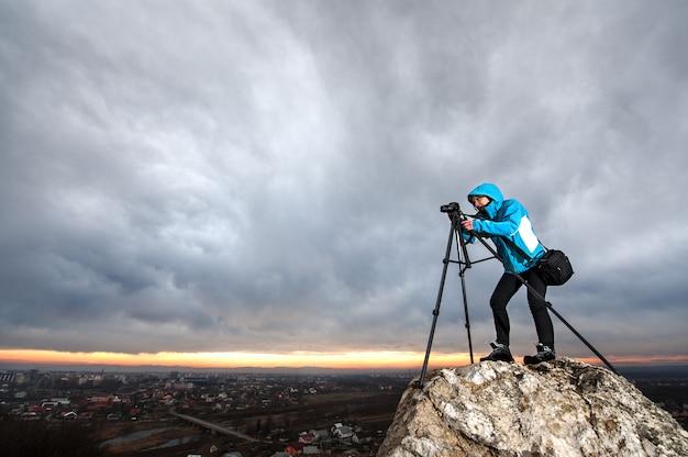 O fotógrafo está de pé com sua câmera no tripé na rocha grande no ponto de visão geral da cidade