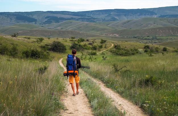 O fotógrafo está descendo a estrada para a montanha. um homem com uma mochila e um tripé se move ao longo da estrada