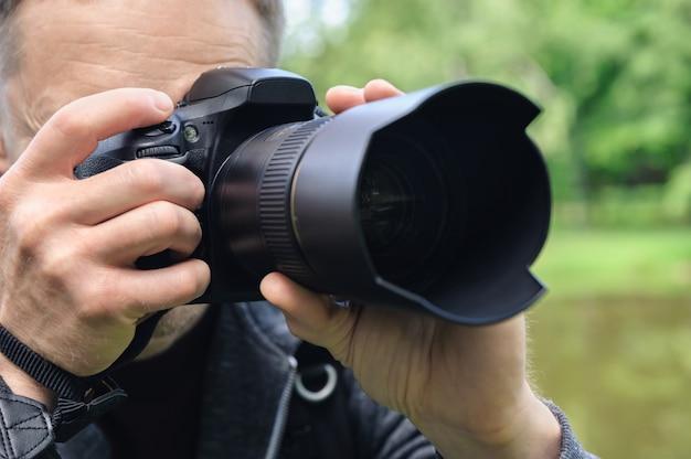 O fotógrafo está fotografando com a câmera.