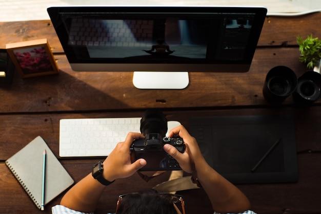 O fotógrafo está na mesa. ele pegou a câmera e viu as fotos que havia tirado.