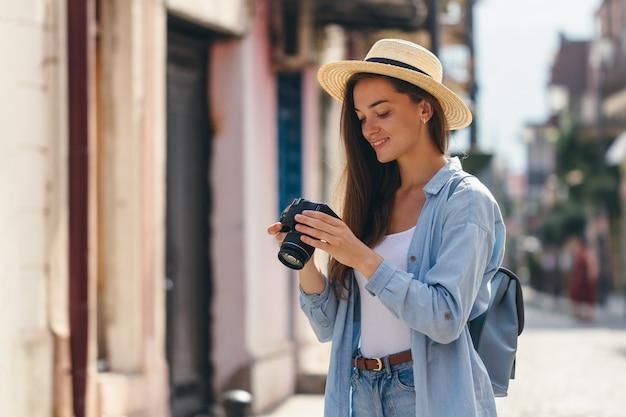 O fotógrafo feliz viajante no chapéu tira fotos de pontos turísticos enquanto caminhava pela rua de uma cidade europeia. estilo de vida em viagem