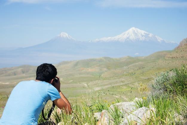 O fotógrafo fotografa a montanha sob o céu azul