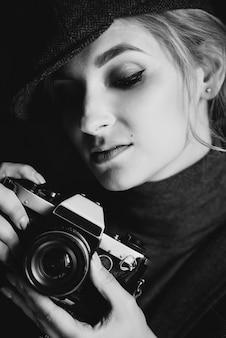 O fotógrafo loiro de menina bonita em terno rigoroso e cappie está segurando um velho camerin retrô nas mãos dela.