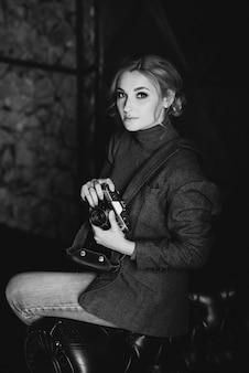 O fotógrafo loiro de menina bonita no terno estrito tem em suas mãos a câmera retro velha. foto em preto e branco