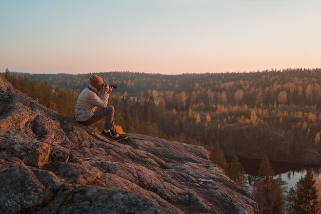 O fotógrafo na rocha tira uma foto da paisagem de outono.