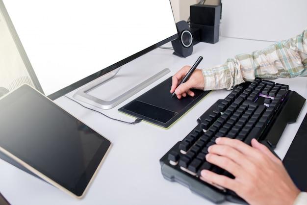O fotógrafo profissional e o design gráfico trabalham na edição de fotos em um tablet pen touch. foto de retoque do editor. monitor de tela branca.