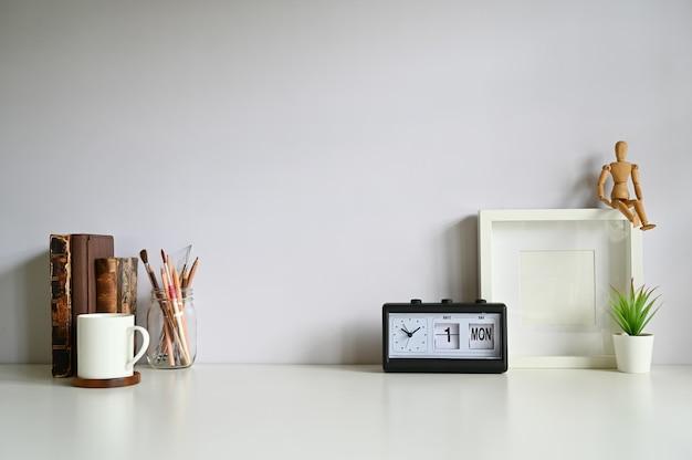 O frame da foto do espaço de trabalho, café, alarme, livros com planta decora na tabela branca.