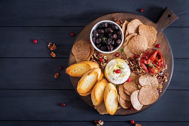 O francês tradicional cozeu o queijo do camembert com tomilho e brinde, nozes, azeitonas, sol secou tomates, e microplaquetas de linho.