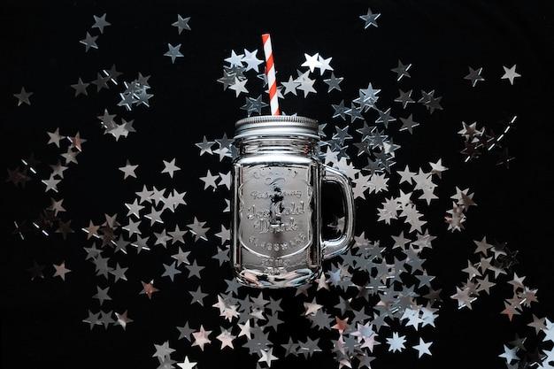 O frasco de pedreiro com estrela de prata polvilha confetes no fundo preto. fundo de natal