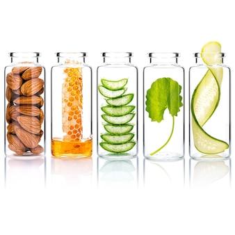 O frasco de vidro de produtos caseiros para a pele e esfoliantes corporais com ingredientes naturais isolados no fundo branco.
