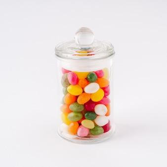 O frasco de vidro encheu-se com os doces e o caramelo com a tampa fechado no fundo branco.