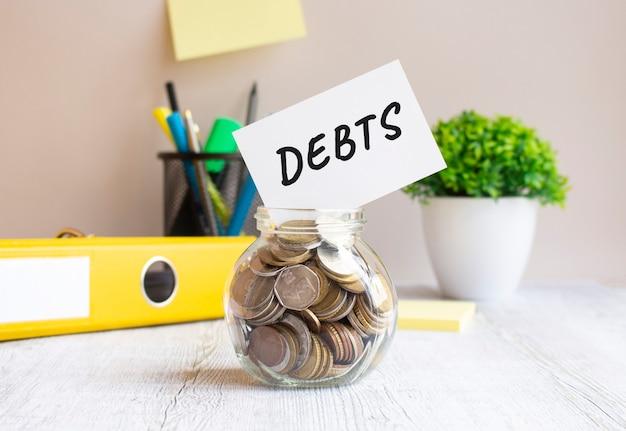 O frasco de vidro está cheio de moedas. no banco existe um cartão com a inscrição debts. tudo está localizado na mesa do escritório. conceito financeiro.