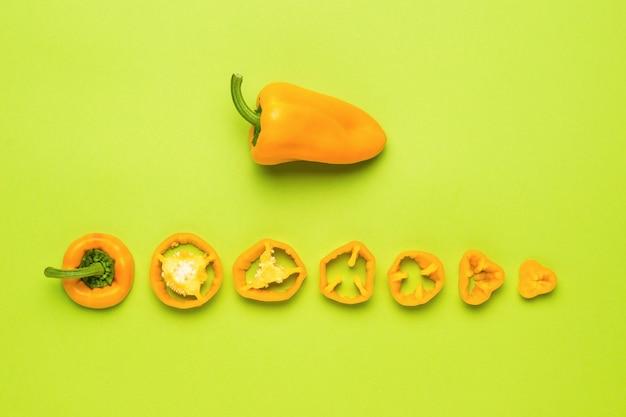 O fruto de uma pimenta inteira e cortado em pedaços sobre um fundo verde. comida vegetariana.