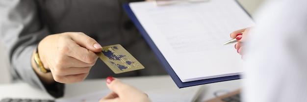 O funcionário dá ao cliente um cartão bancário de plástico e um documento para o conceito de serviços bancários de assinatura