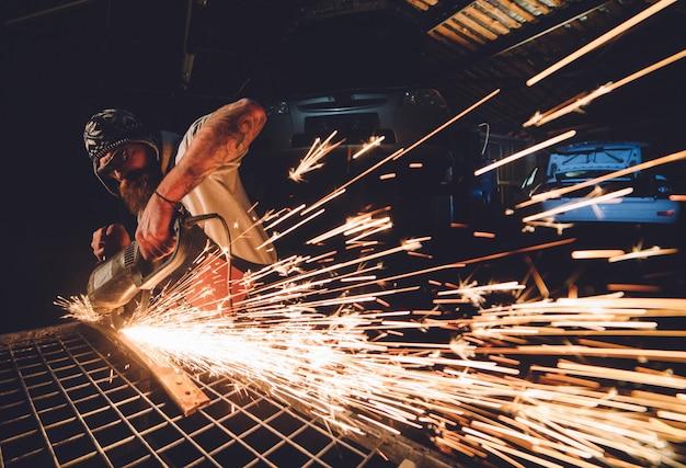 O funcionário da estação de serviço produz reparo do corpo com uma máquina de solda em faíscas nas mãos