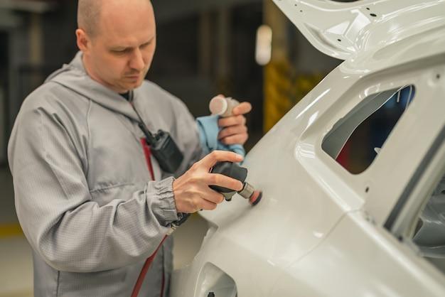 O funcionário da oficina pinta a carroceria do carro lixando a parte pintada de uma ferramenta pneumática