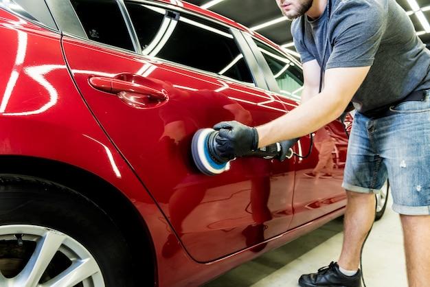 O funcionário do serviço automotivo dá brilho aos detalhes do carro com polidor orbital