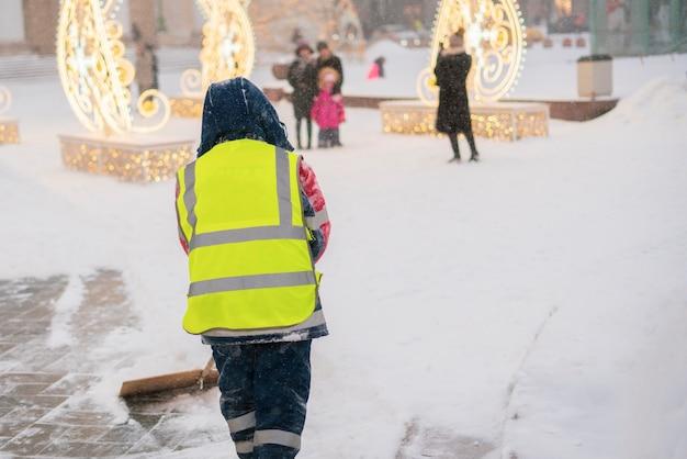 O funcionário do serviço municipal limpa a neve das ruas com a pá ãƒâ â °