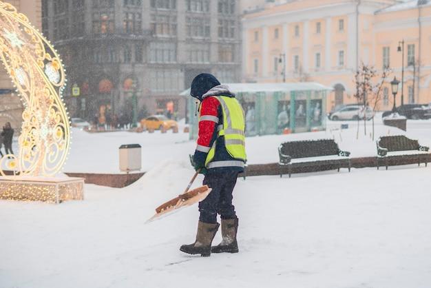O funcionário do serviço municipal limpa a neve das ruas com a pá b