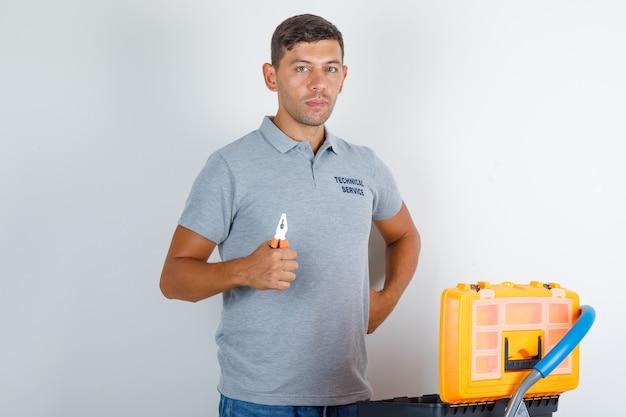 O funcionário do serviço técnico procura a ferramenta com a caixa de ferramentas enquanto segura a ferramenta e parece ocupado