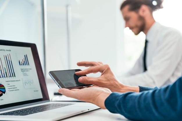 O funcionário está usando seu smartphone para verificar os dados financeiros