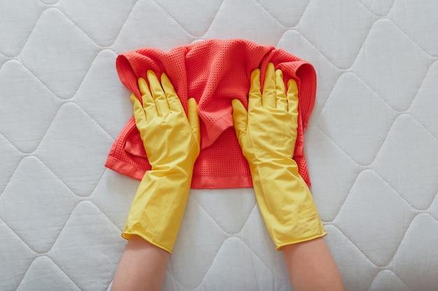 O funcionário limpa a superfície do colchão na cama com um pano. limpeza de superfícies de desinfecção. limpeza pessoal da empresa mãos nas luvas de borracha fazem a limpeza química do colchão.