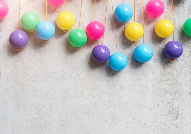 O fundo abstrato das bolas coloridas pendura no muro de cimento cinzento. festa e comemorando