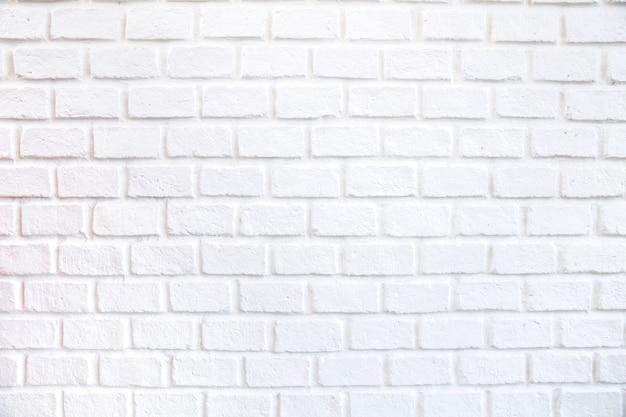 O fundo branco do grunge da textura da parede de tijolo com cantos vignetted, pode usar-se ao design de interiores.