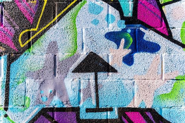 O fundo com textura da parede pintou setas e grafittis coloridos.
